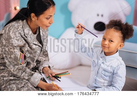 My favorite color. Enthusiastic diligent lively child drawing some things in a notebook using pencils and sitting comfortably on the floor