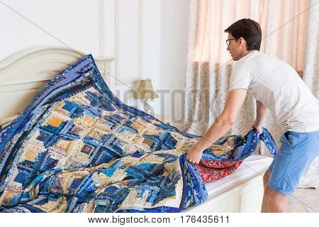 handsome young man making bed a color patchwork quilt in the white interior. scrappy blanket on the bed closeup.