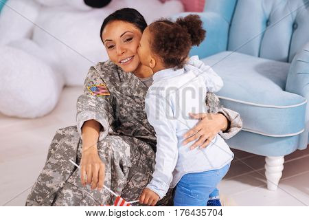 I love you this much. Active attached gorgeous girl kissing her mom on her cheek while she sitting on the floor beside her and holding a flag in her hand