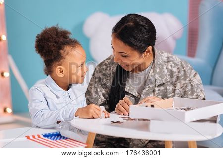 Family leisure. Charismatic attentive amazing mom and child spending their weekend together and completing a nice picture while sitting at the white table together