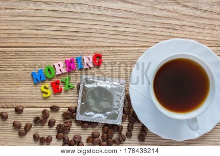 morning sex words condom and a cup of coffee. coffee beans on old wooden table