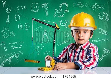 cute indian baby boy playing with toy crane wearing yellow construction hat or hard hat, childhood and education concept, with doodles drawn over green chalkboard