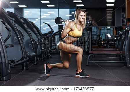 Sexy young athletics girl doing squat with barbell on her shoulders. Fitness woman in yellow sport clothing workout with barbell in gym