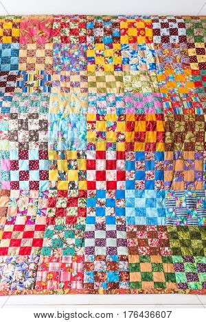 Part of symmetric geometry pattern color patchwork quilt as background. Scrappy blanket with pattern of small squares. Handmade.