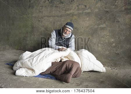 Mature homeless man sitting in an old dirty blanket