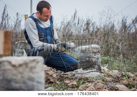 Caucasian man builder working with circular saw outdoors, sawdust flying around, telephoto shot