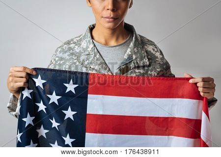 Hold on to my beliefs. Stunning resolute confident lady doing a photoshoot for military advertisements while wearing her uniform and holding up Stars and Stripes