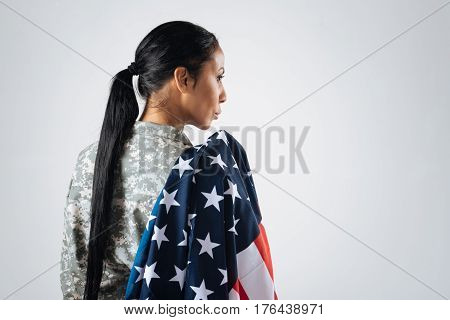 Loyal and beautiful. Gorgeous pretty continent lady holing the national flag over her shoulder and looking strong and brave while working for a professional photographer