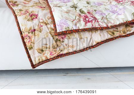 Part of color patchwork quilt with vintage flowers pattern lying on a white sofa as background. Colorful Scrappy blanket. Empty spase for the text.