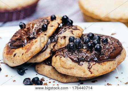 Pancakes stuffed with blueberry jam and sprinkled with blueberries on white plate on wooden table