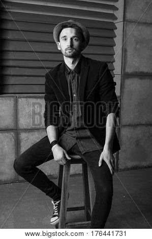 Stylish l guy in black and white hat sits on a high chair. Black and white background