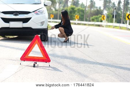 Business women driver changing tire on her car.