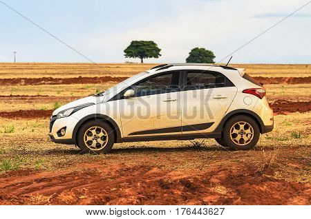 Side View Of A White Car On A Dirt Road