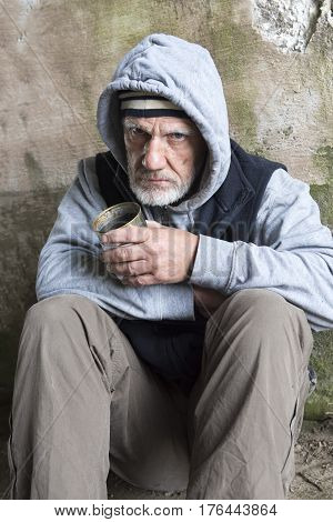 Homeless man begging outdoors with a tin