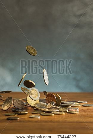 The silver and golden coins and falling coins on wooden table background