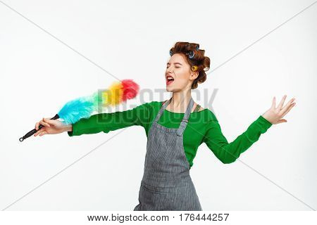 Funny nice woman perfomances at camera holding duster and singing songs