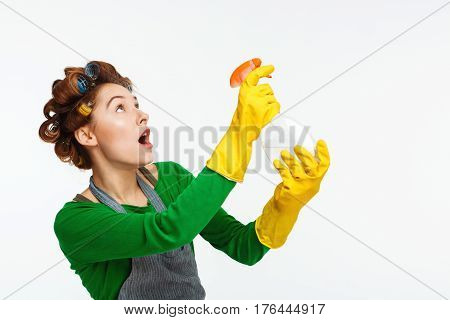 Youn nice woman in yellow rubber uses spray while cleaning up house posing for camera