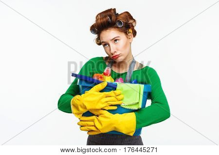 Young pretty red haired woman with curlers holds cleaning tools with sad face making fun