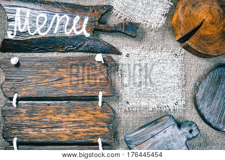 Dark wood boards, wood slice and burlap pieces as frames on burlap background. Wooden signboard with text 'Menu' as title bar. Rustic style template for food and drink industry