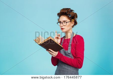 Nice young girl with curlers on hair and glasses on face dived into reading book