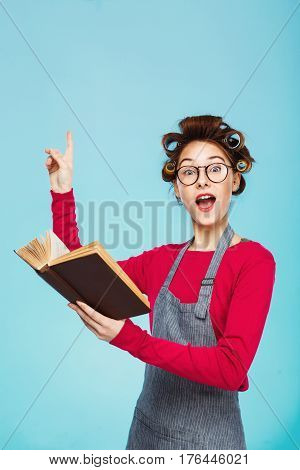 Funny attractive girl in pink with glasses and curlers reads book thinking deeply