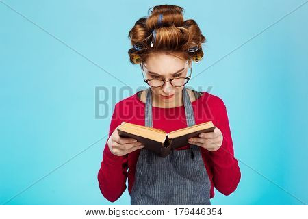 Nice young girl reads book wearing glasses apron and with curlers on hair while cleaning