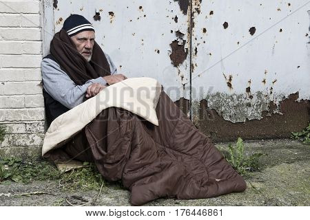 Mature homeless man in a dirty sleeping bag out on the streets