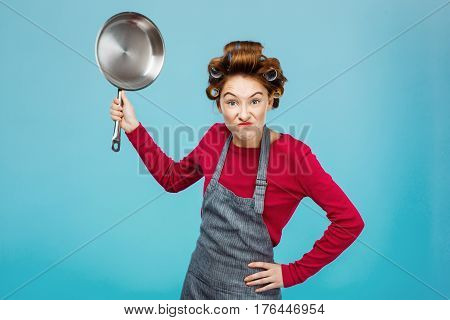 Nice young girl tries to scare you with big iron frying pan in hands