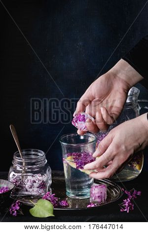Femail hands put ice cubes with flowers into glass of lilac lemonade with lemon. Glass jar of sugared lilac flowers and pitcher on black tablecloth over black. Dark rustic atmosphere. See series.