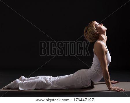 Woman exercising yoga indoor on black background,Cobra Pose/Bhujangasana
