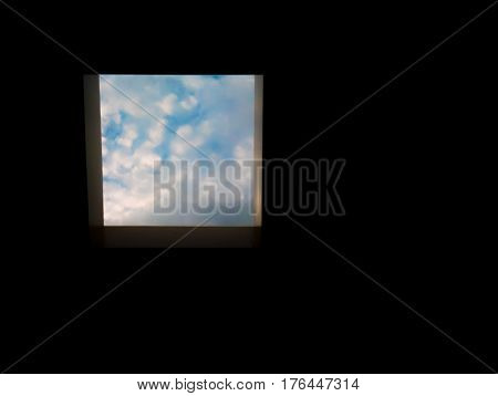 looking out a skylight to blue and cloudy sky