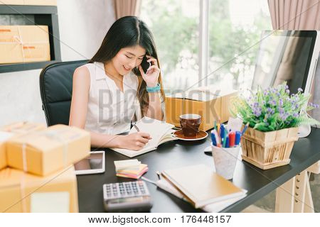 Young Asian small business owner working at home office using mobile phone and taking note on purchase orders. Online marketing packaging delivery startup SME entrepreneur or freelance woman concept