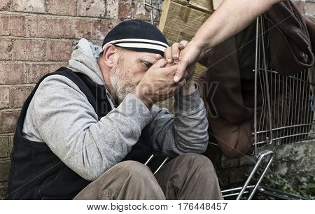 Mature homeless man holding an unrecognisable woman's hand