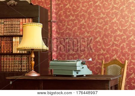 Typewriter, lamp, books, chair - on a red vintage background