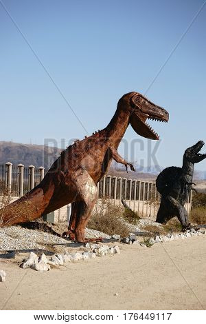 YUCCA VALLEY, UNITED STATES - DECEMBER 24, 2015: Large welded dinosaur sculptures are standing in front of a workshop on the edge of the road on December 24, 2015 in Yucca Valley.