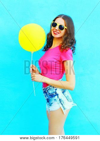 Fashion Pretty Smiling Young Woman Wearing A T-shirt, Denim Shorts With Yellow Air Balloon Over Colo