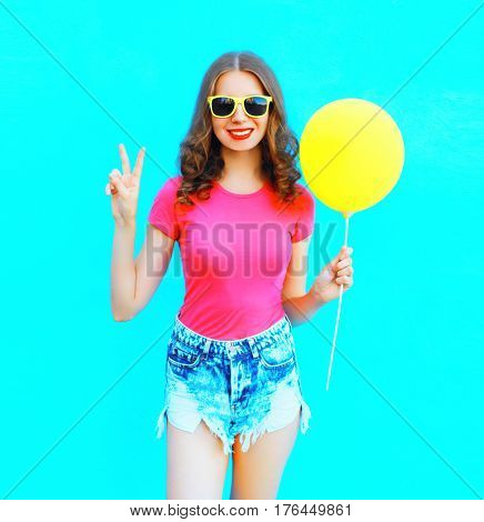 Fashion Smiling Woman Wearing A T-shirt, Denim Shorts With Yellow Air Balloon Over Colorful Blue Bac