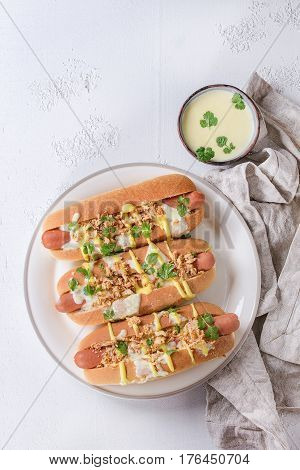 Hot dogs with sausage, fried onion, coriander leaves, cheese sauce and mustard, served on white ceramic plate with textile over white concrete texture background. Fast food. Top view, copy space