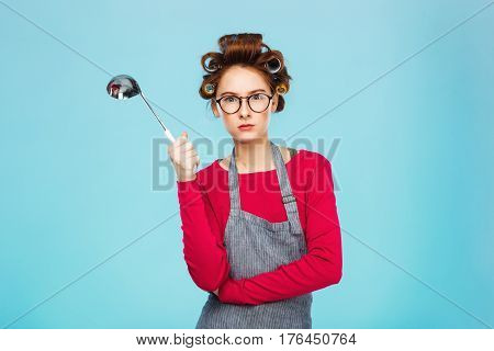 Nice funny girl hides from dangerous ladle and standing on blue background