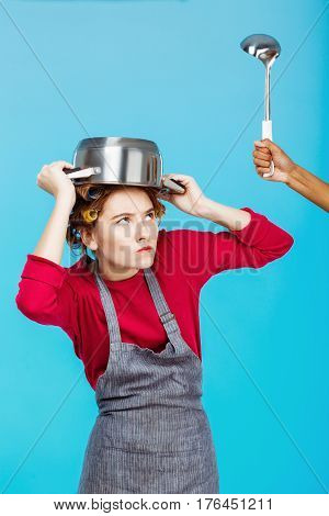 Nice young woman with saucepan on head hides from hand with ladle