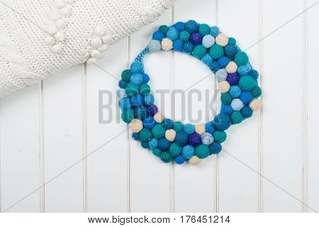 Felted wool necklace on the wooden background.Colorful blue necklace for modern women.