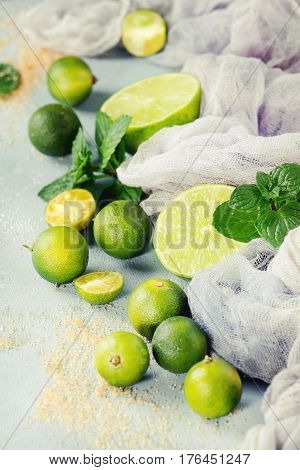 Ingredients for mojito cocktail, whole, sliced lime and mini limes, mint leaves, brown crystal sugar over gray stone texture background with gauze textile. Close up