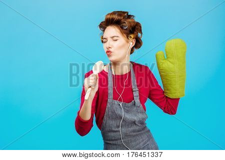 Cute young girl sings songs holding spoon in hand and listening to music in headphones