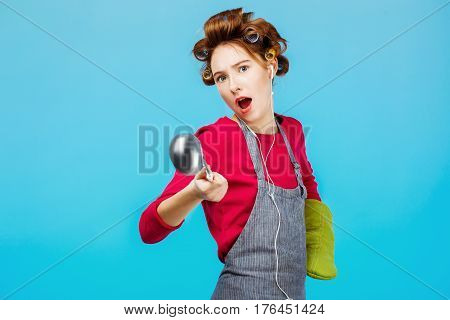 Young funny girl dancesand sings while cooking dinner with green glove on hand