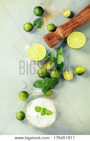 Ingredients for mojito cocktail, whole, sliced lime and mini limes, mint leaves, brown crystal sugar over gray stone texture background with wooden bar muddler, glass full of ice. Top view, space