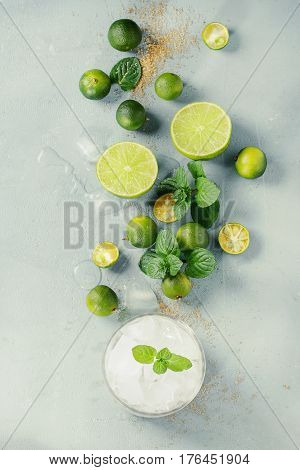 Ingredients for mojito cocktail, whole, sliced lime and mini limes, mint leaves, brown crystal sugar over gray stone texture background with glass full of ice. Top view, space