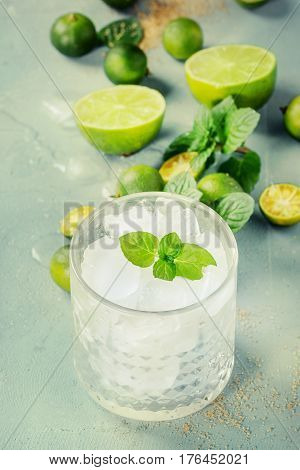 Ingredients for mojito cocktail, whole, sliced lime and mini limes, mint leaves, brown crystal sugar over gray stone texture background with glass full of ice. Space for text