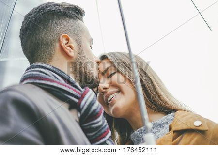 Beautiful young couple standing close to each other under an umbrella on a rainy day - Man kissing his girlfriend on the forehead - Boyfriend and girlfriend having tender moments in the rain
