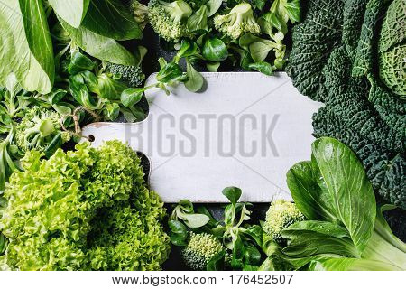 Variety of raw green vegetables salads, lettuce, bok choy, corn, broccoli, savoy cabbage as frame round empty white chopping board. Food background. Top view, space for text