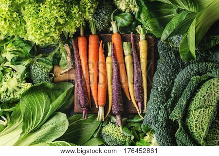 Variety of raw green vegetables salads, lettuce, bok choy, corn, broccoli, savoy cabbage, colorful young carrots on wooden chopping board. Food background. Top view, space for text